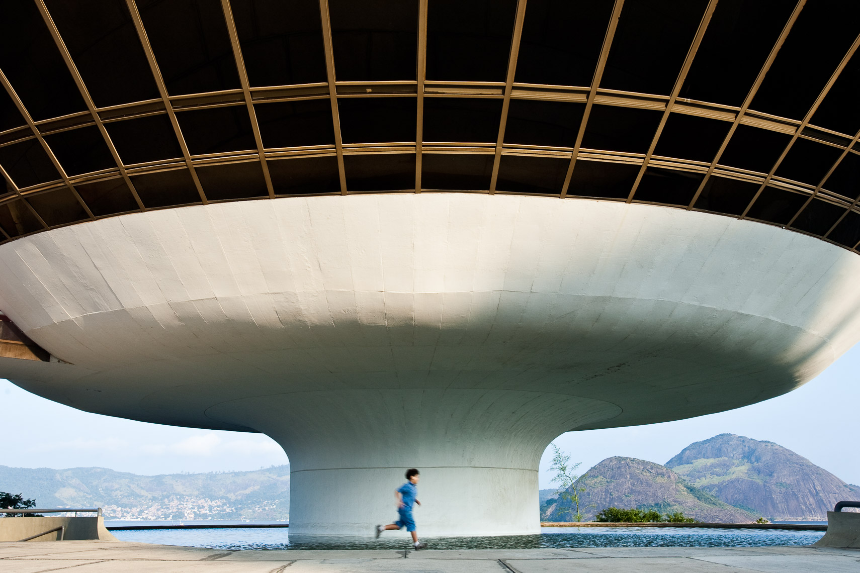 Child running in front of UFO shaped building at the edge of bay surrounded by mountains