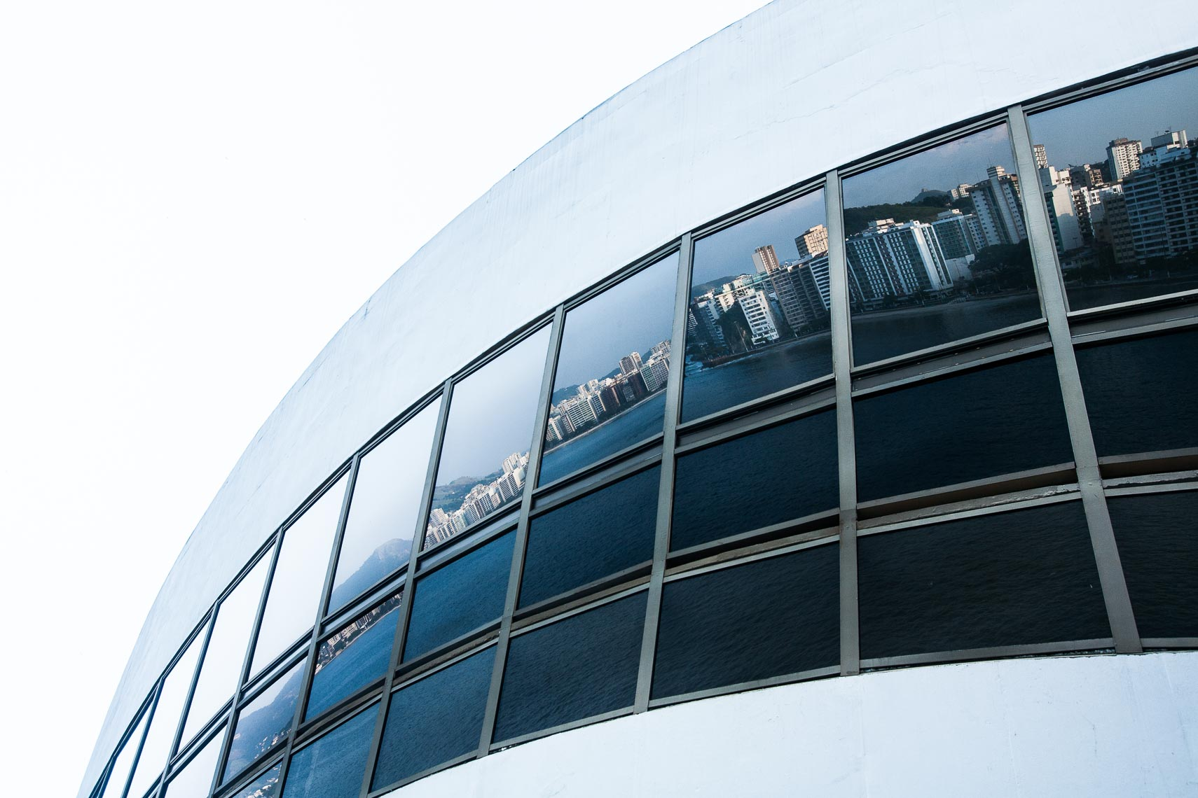 Urban landscape reflected in glass of curved building