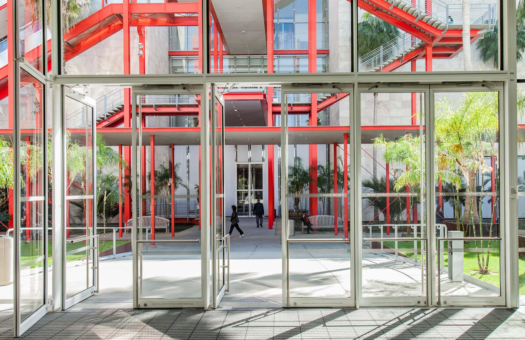 Glass doors open to a walkway with red stairways