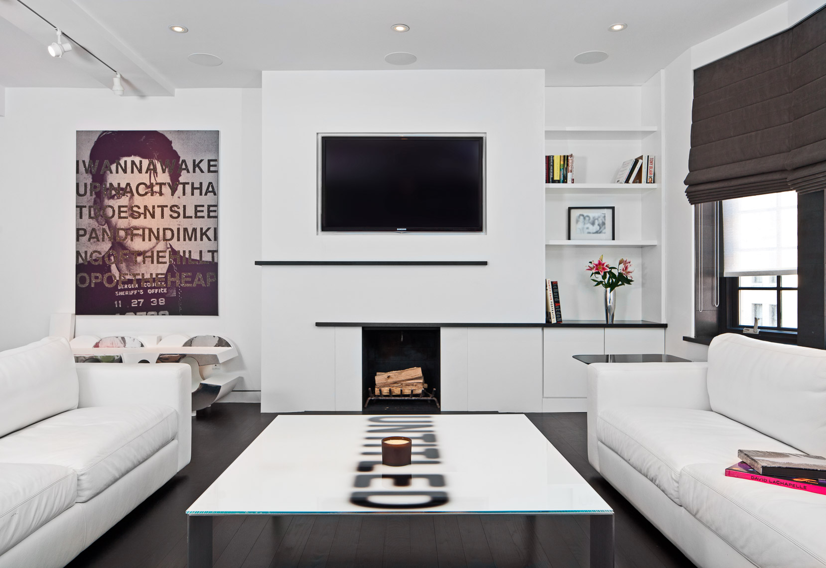 Interiors of a white walled upscale living room with art on the walls