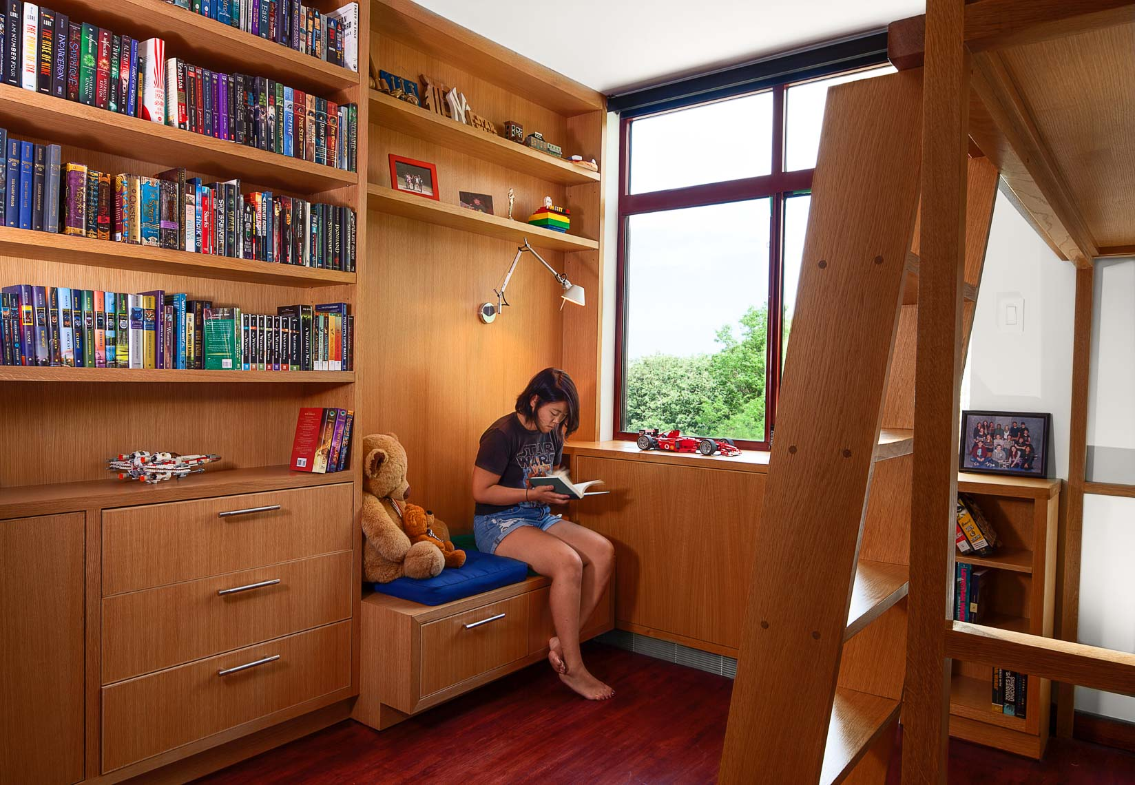 Girl reading a book in a wood paneled study with book shelves