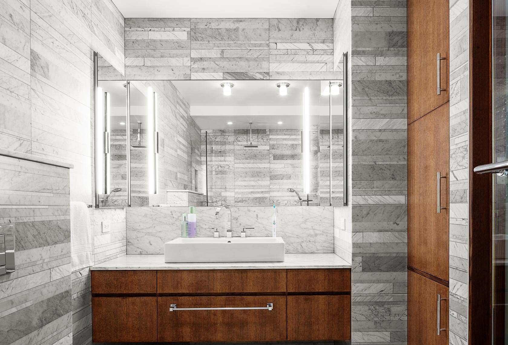 A marble tiled bathroom vanity inside a luxury apartment