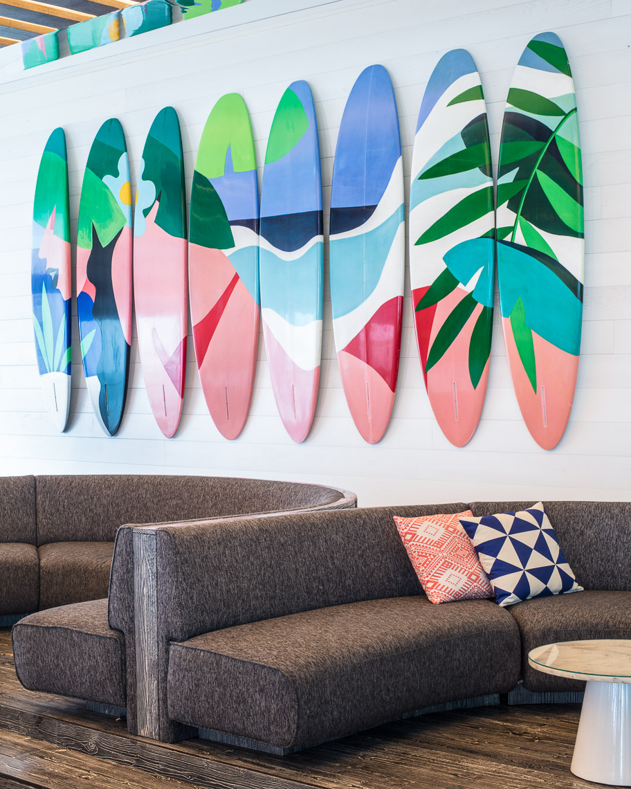 Colorful art on surfboards adorn the walls of a seating area with curved couches