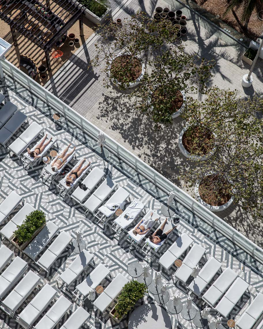 Overhead shot of sunbathers on luxury hotel patio