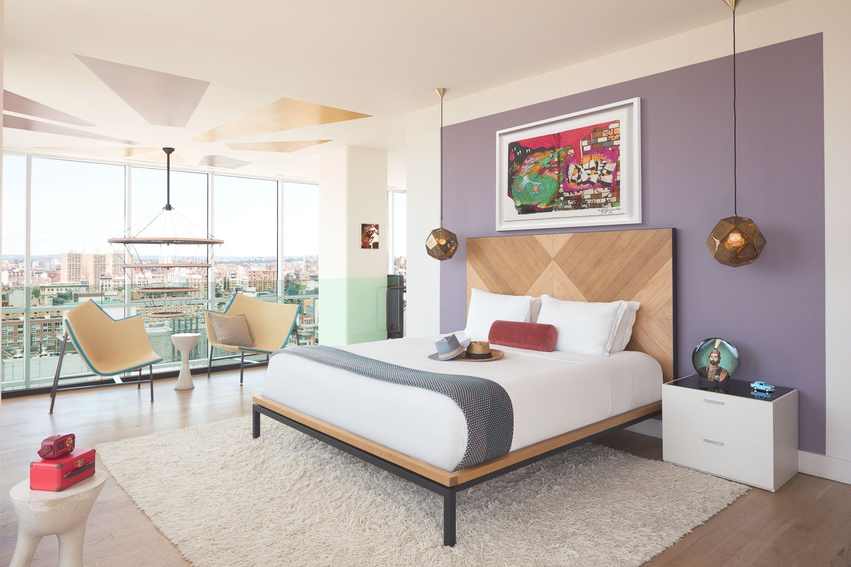 Hotel room with panoramic city views and large graffiti artwork on wall