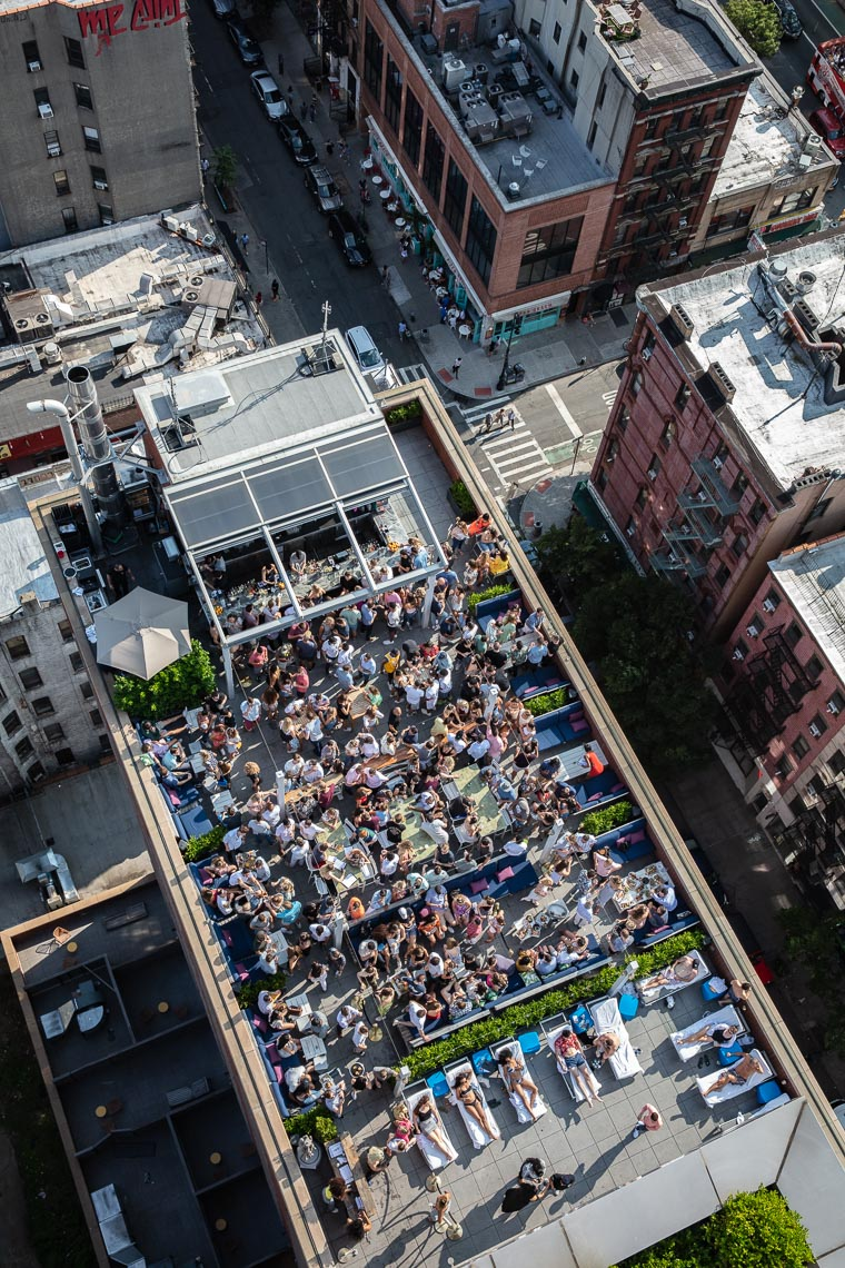 Overhead shot of people in a rooftop hotel bar in summer