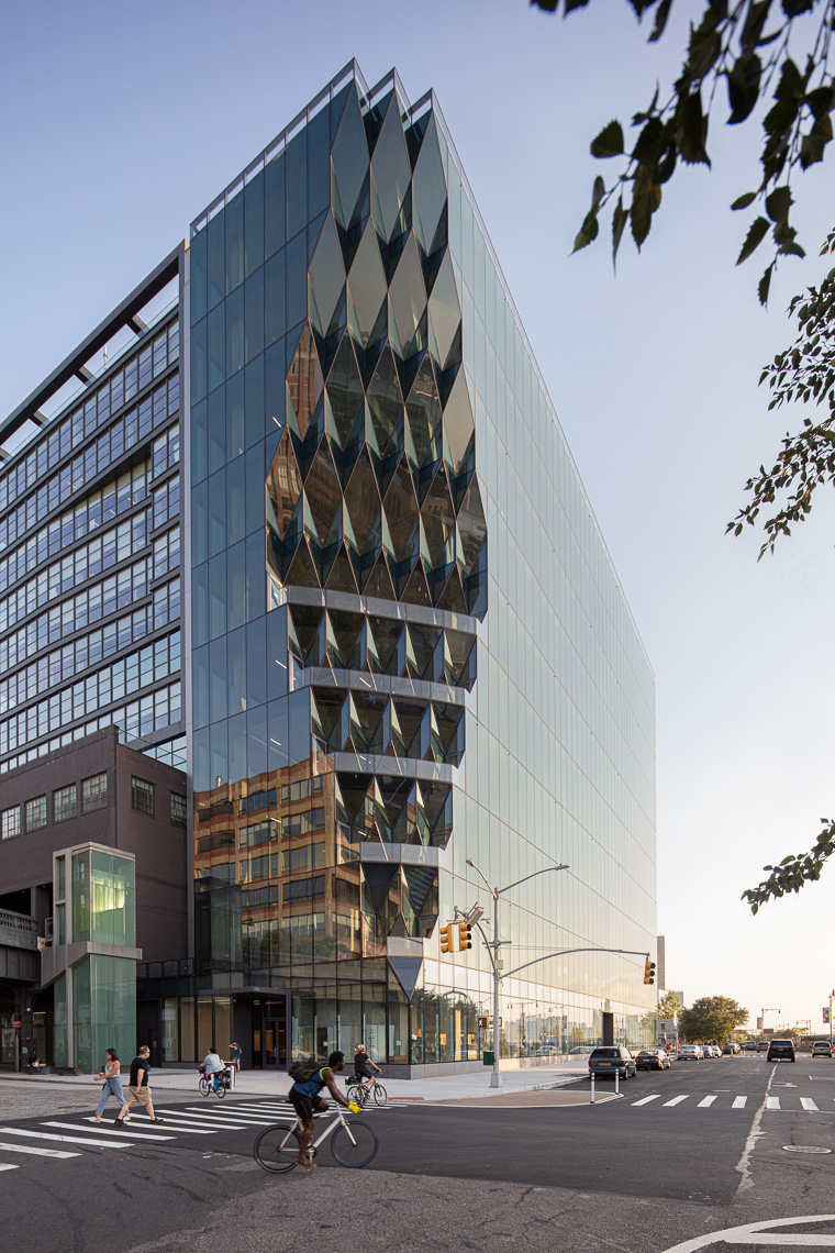 Street view of sculpted geometric glass exterior office tower