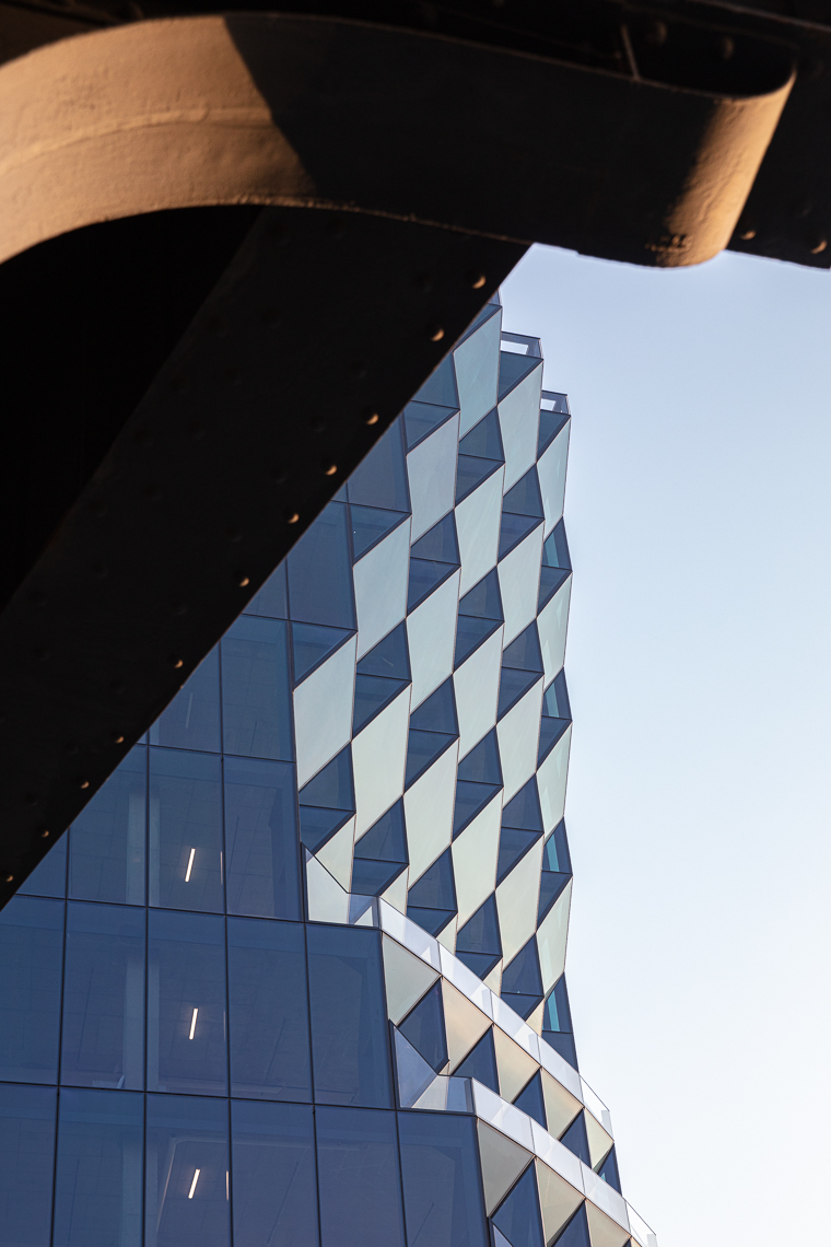 Detail of sculpted geometric glass exterior office tower and High Line park