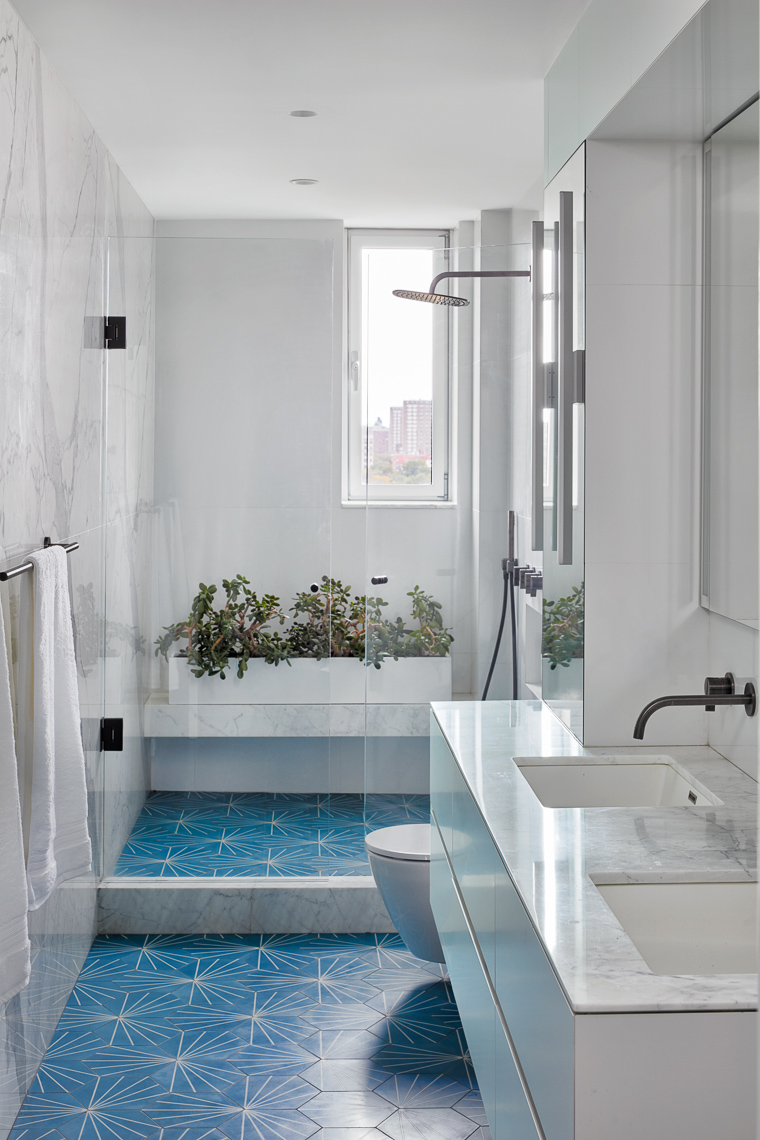 Straight view of white marble and blue tiled bathroom