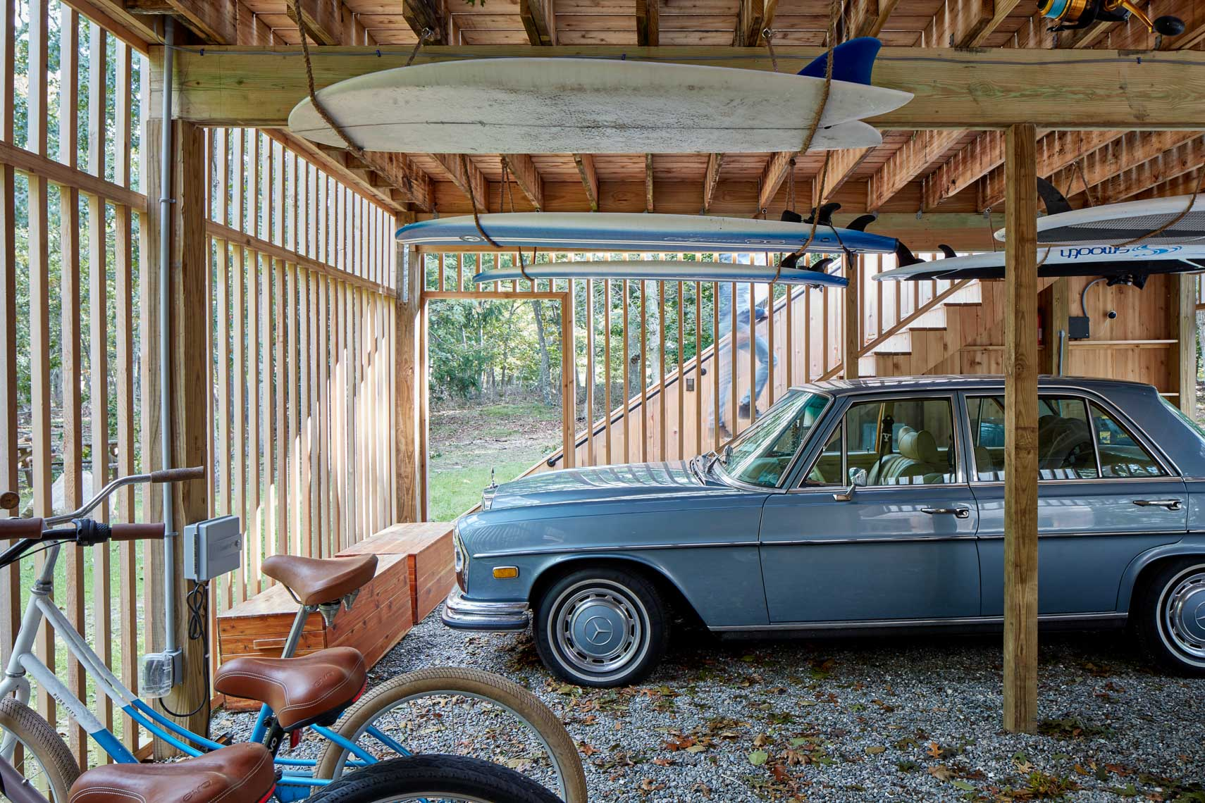 Classic Mercedes Benz in garage with surf boards hanging overhead
