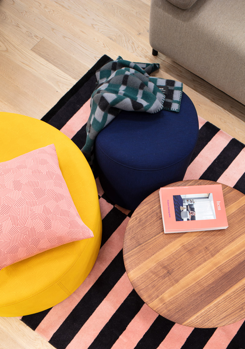 Overhead shot of coffee table, striped carpet, throw blanket and colorful cushion on pouf