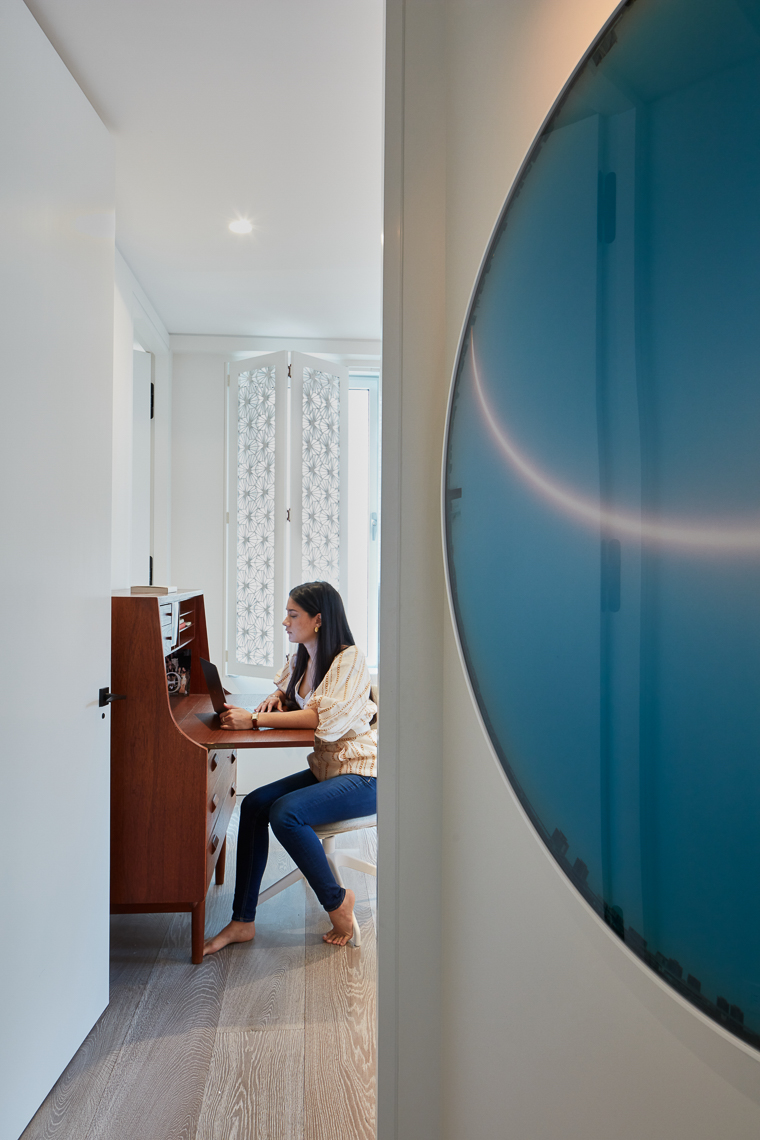 Young woman working on a desk inside a room with round art in foreground