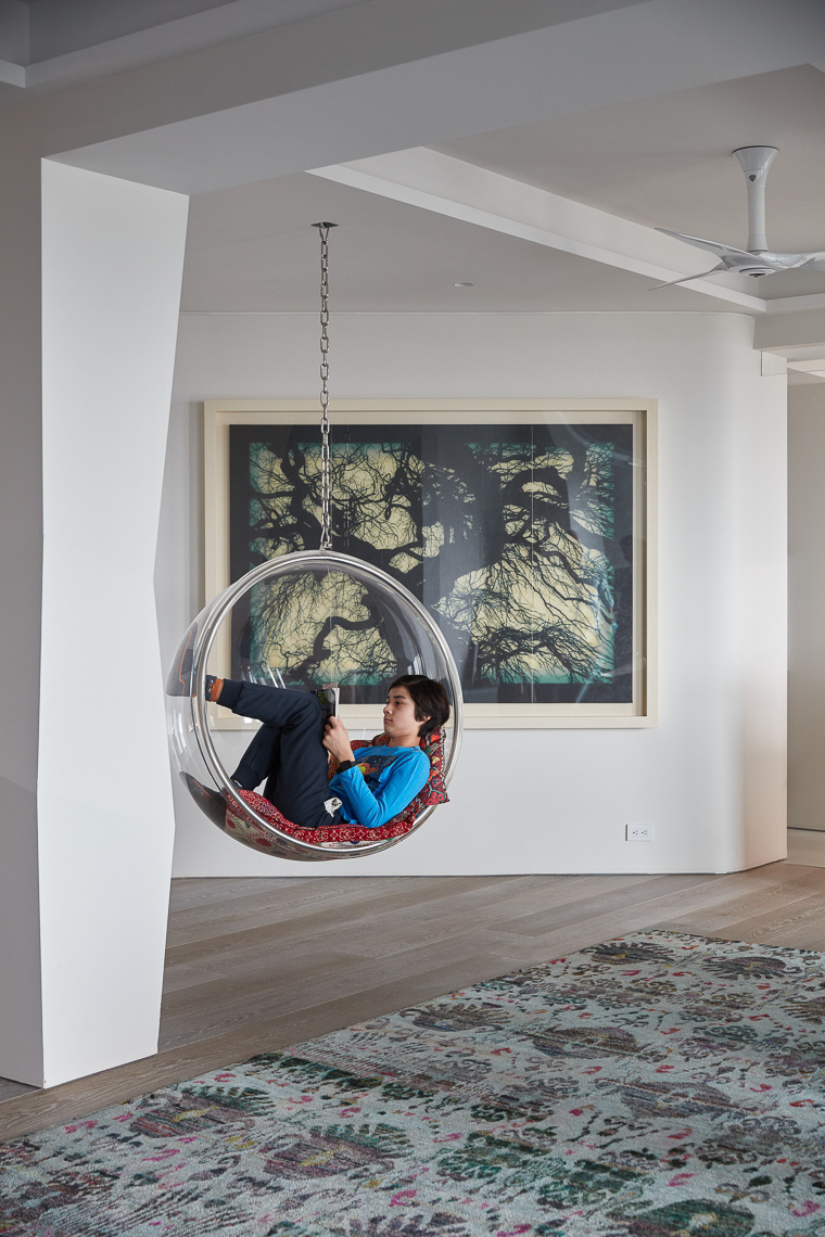 Young boy reading a book inside a hanging Eero Arnio Bubble chair