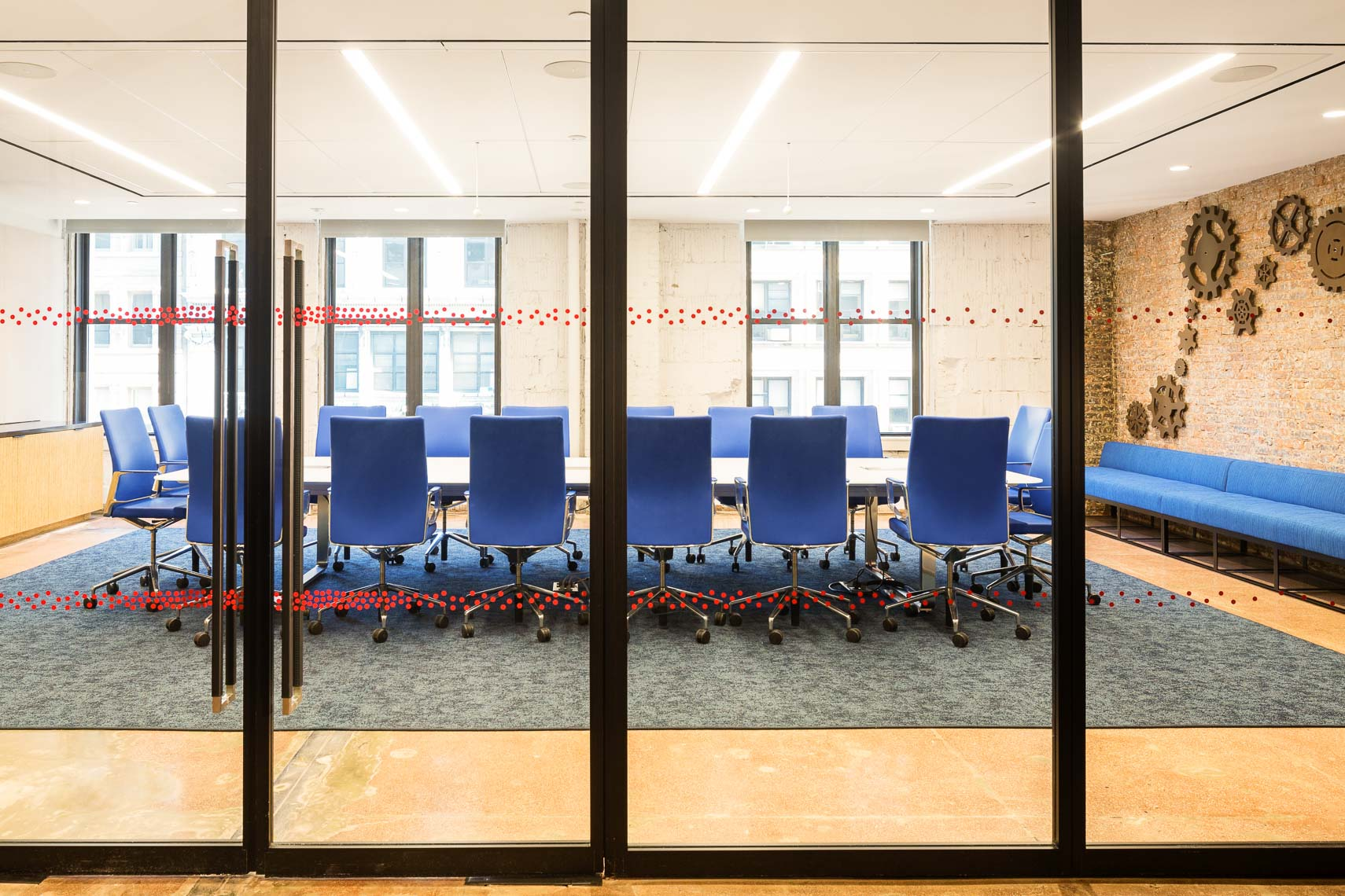 Glass walled conference room with blue chairs