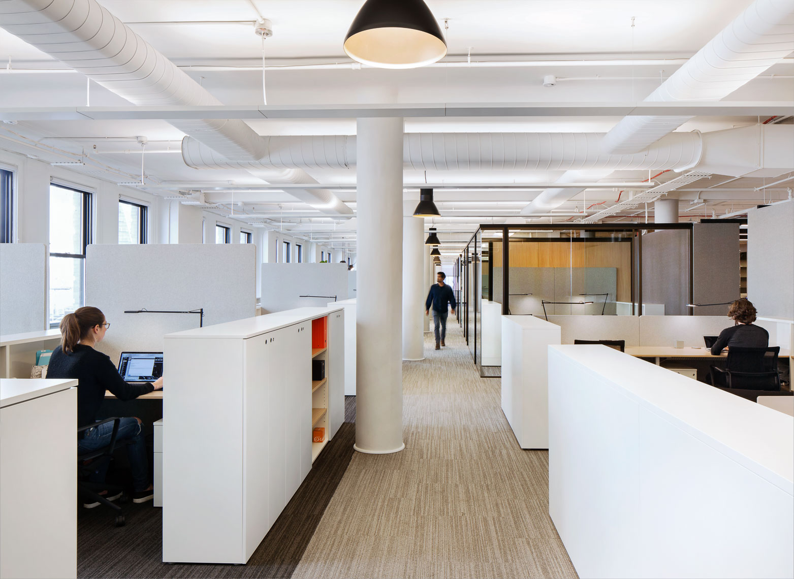 A long white walled hallway flanked by open work areas and private offices