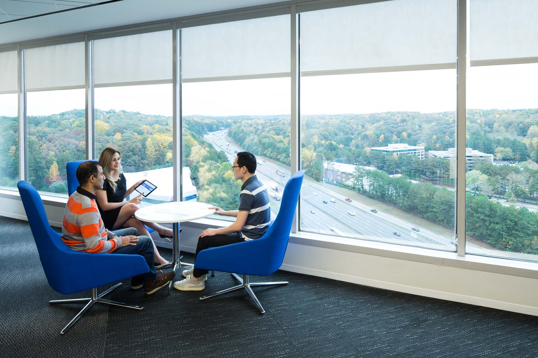 Office employees in a glass walled office overlooking an urban landscape