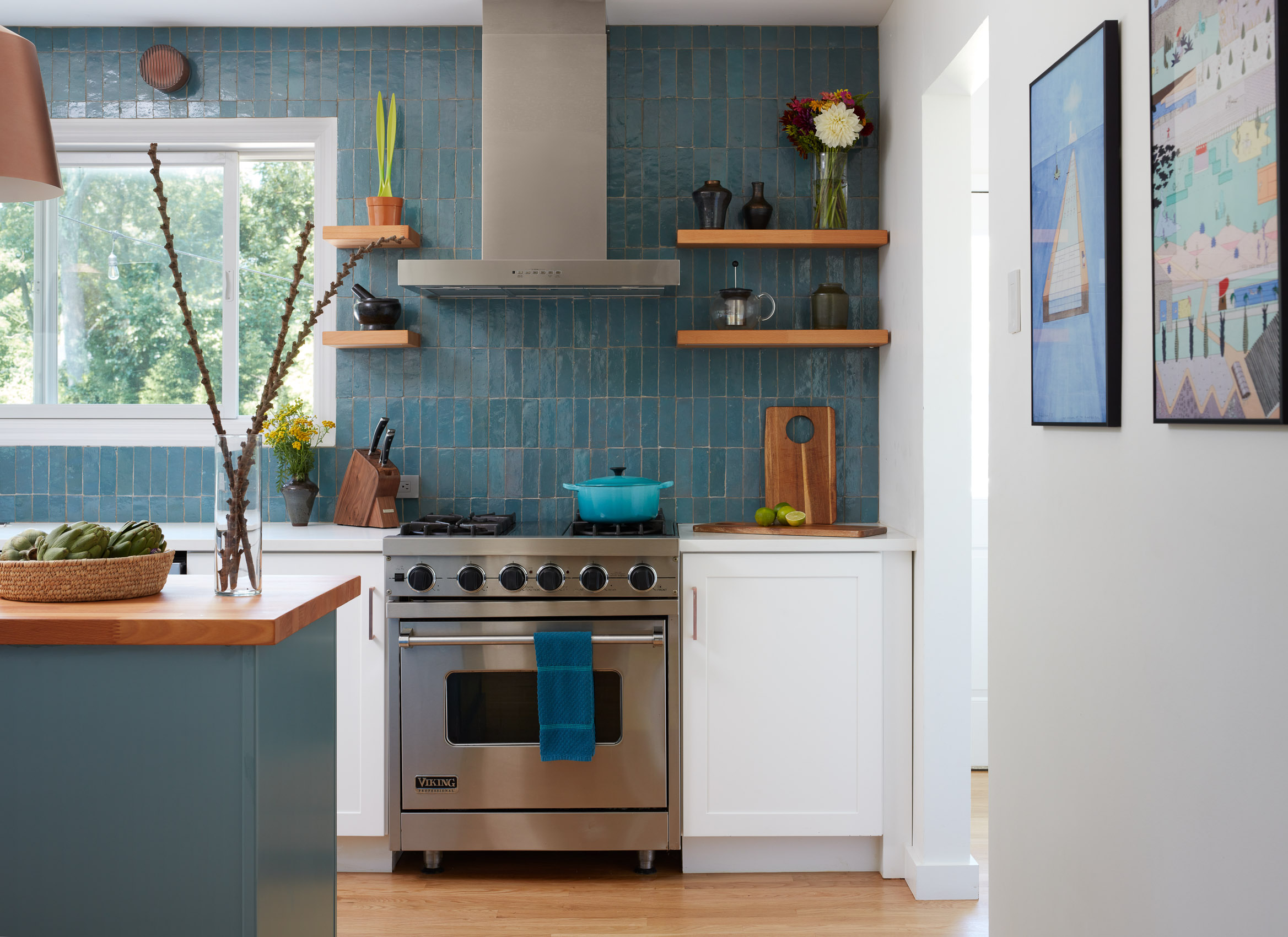 Miele appliances and a backsplash of hand-blown glass tile by Ann Sacks sit within walnut cabinetry with Jamison pulls; the island integrates a Space Theory countertop and Kallista faucet.