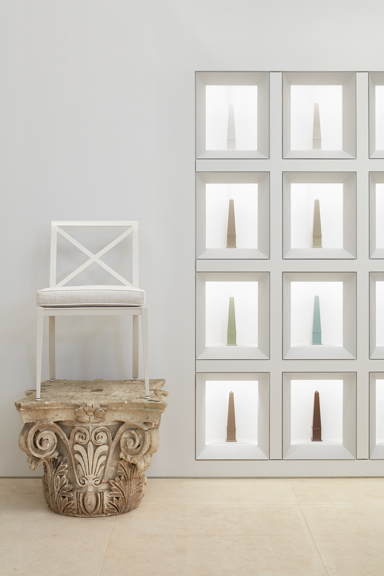 Detail of chair on marble antique capital with product displayed in wall insets