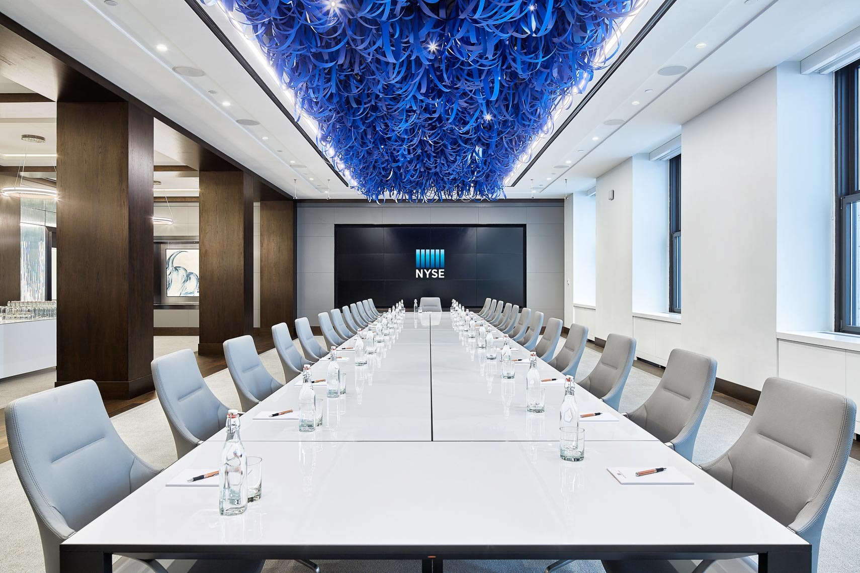 Wide straight view of large conference room table with blue decoration on ceiling