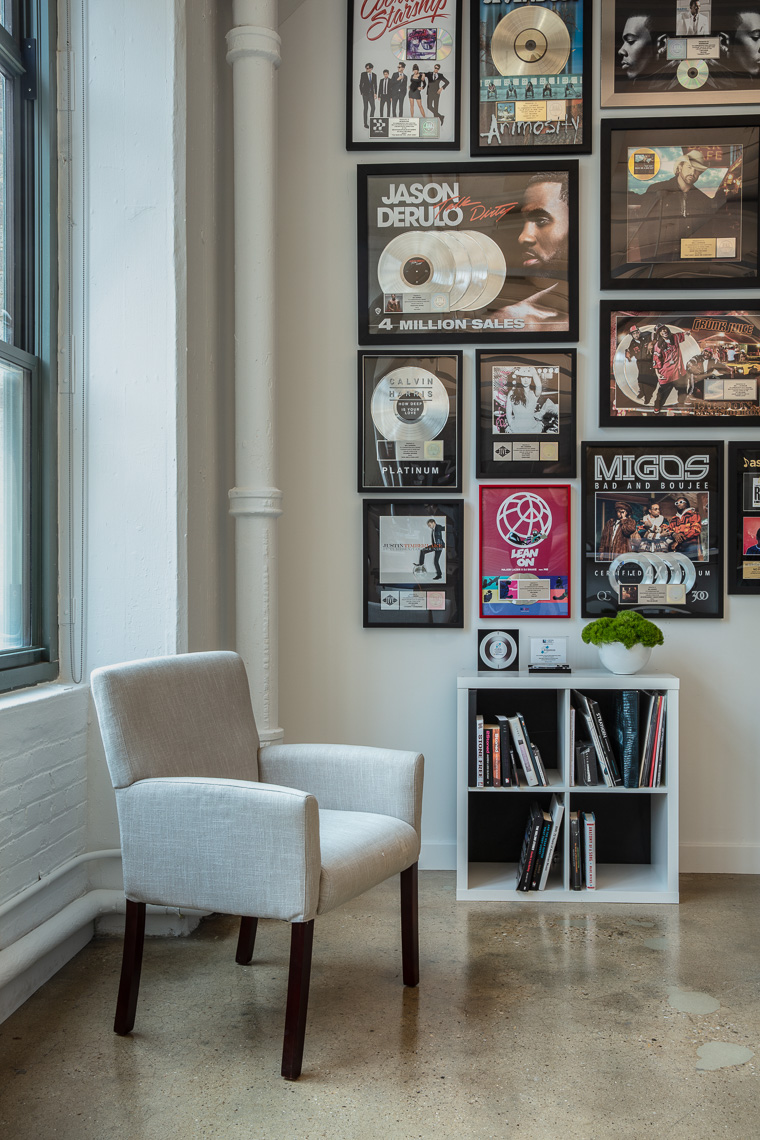 Vignette of wall with platinum record albums and white chair