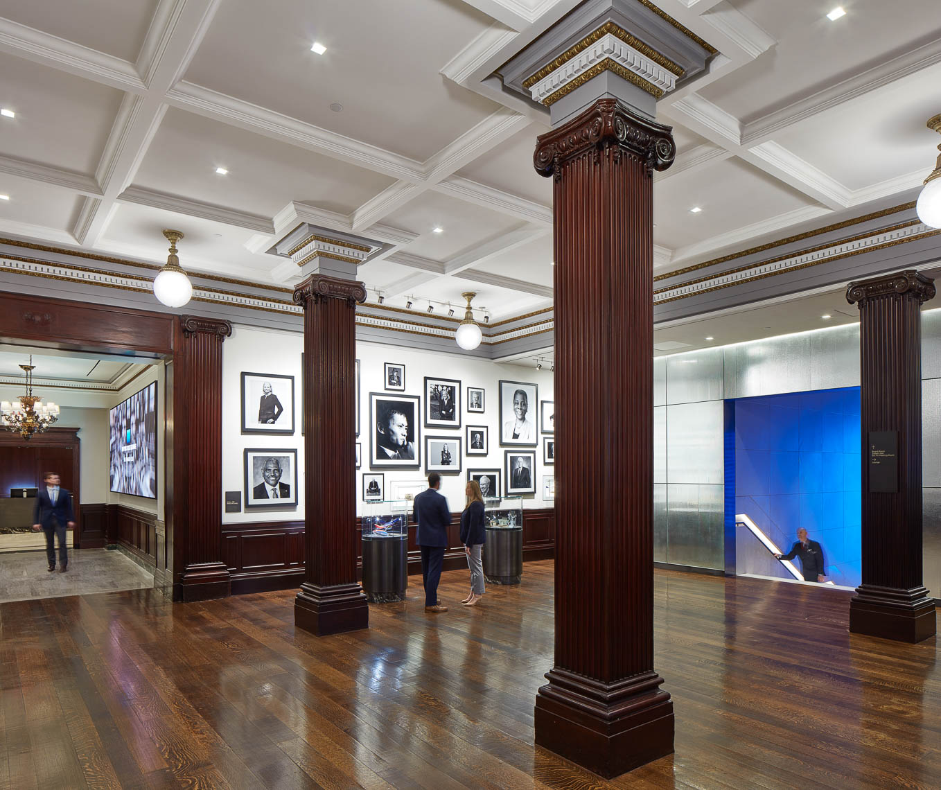 Interiors of common area with traditional wood carved columns and photographs of business leaders on the wall