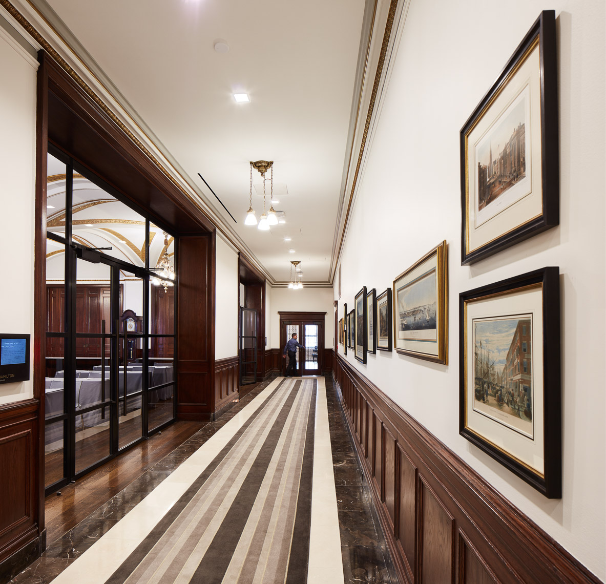 Long wood paneled hallway with historical photographs on wall