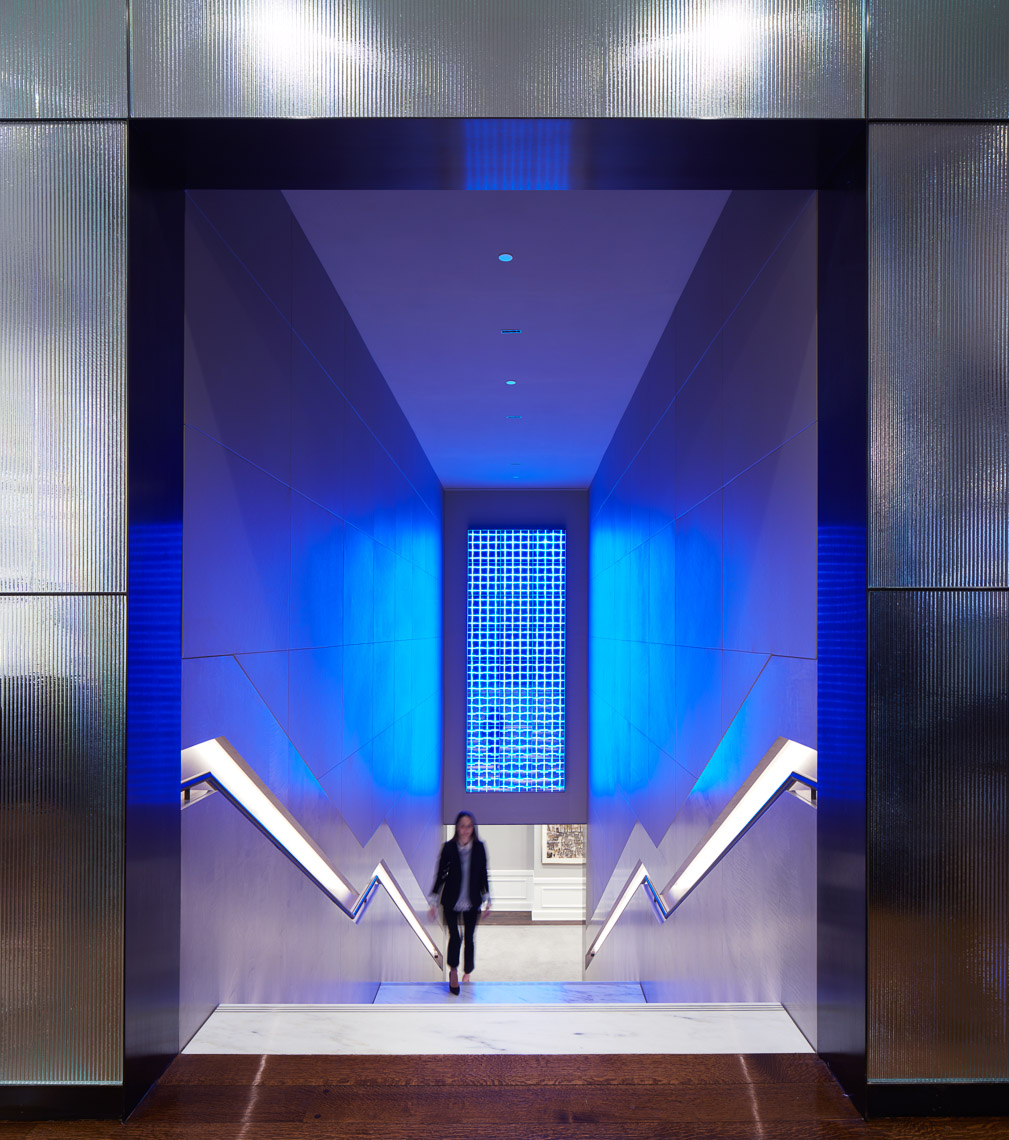 A stunning gilded staircase entryway with blue light LED art
