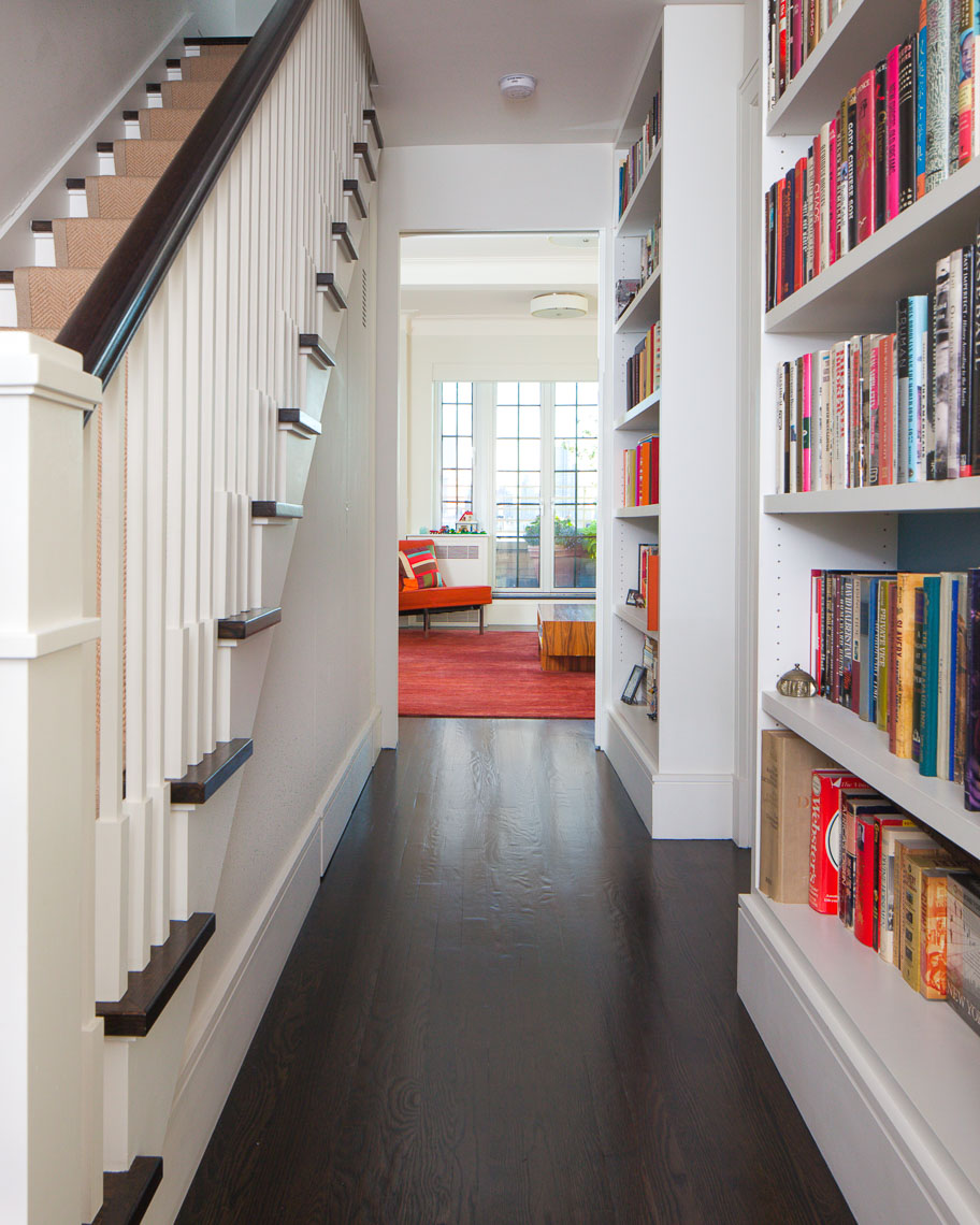 Hallway flanked by a staircase and bookshelf leading to a sitting area