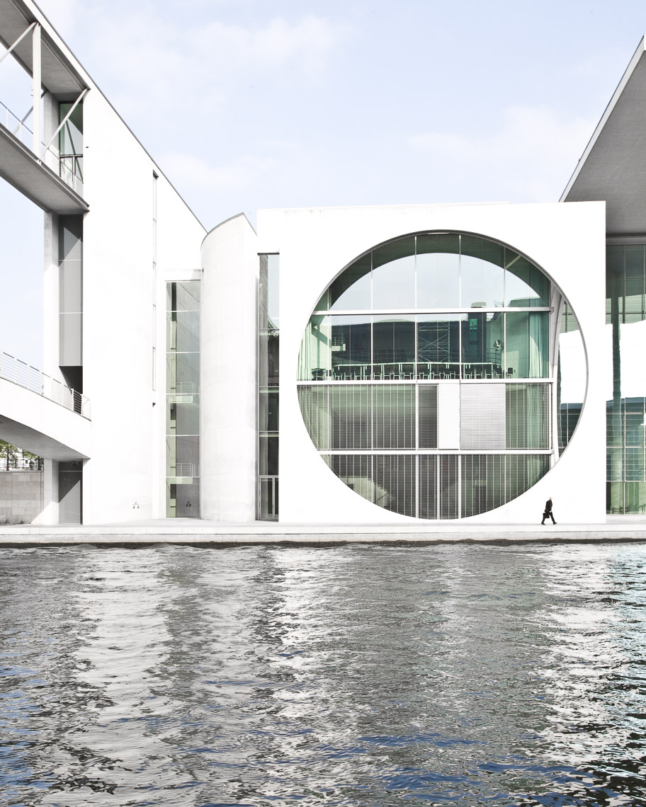 White building with circular opening at the edge of a body of water
