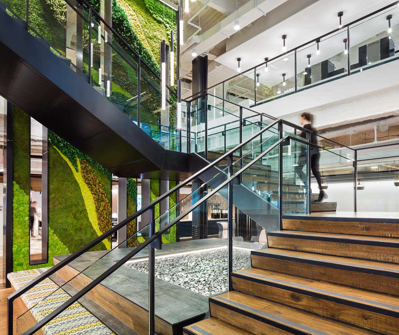 A large wraparound central staircase with green wall panels inside a modern office